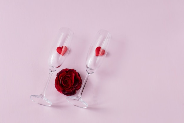Dois copos com corações e um botão de rosa vermelho