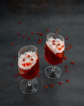 Dois copos com gelatina vermelha, creme wiiped e sementes de romã na parte superior.