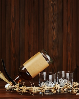 Dois copos com gelo para uísque e uma garrafa na parede de madeira escura.