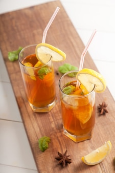 Dois copos com kombuchá e rodelas de limão, canudos e anis estrelado em uma mesa de madeira.