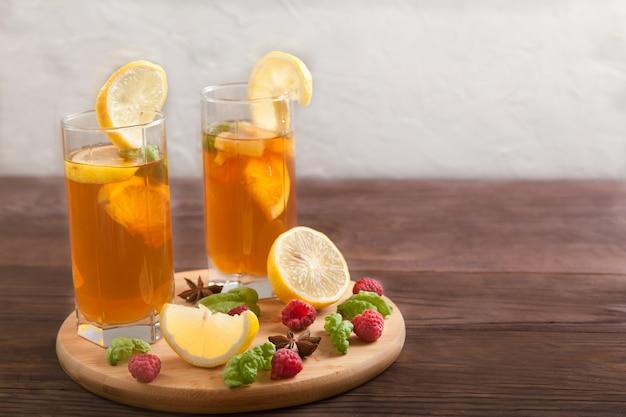Dois copos com kombuchá e rodelas de limão e anis estrelado em uma mesa de madeira.