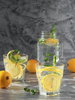 Dois copos com limonada bebem com limão e hortelã.