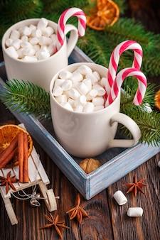 Dois copos com pequenos marshmallows em um fundo escuro de madeira
