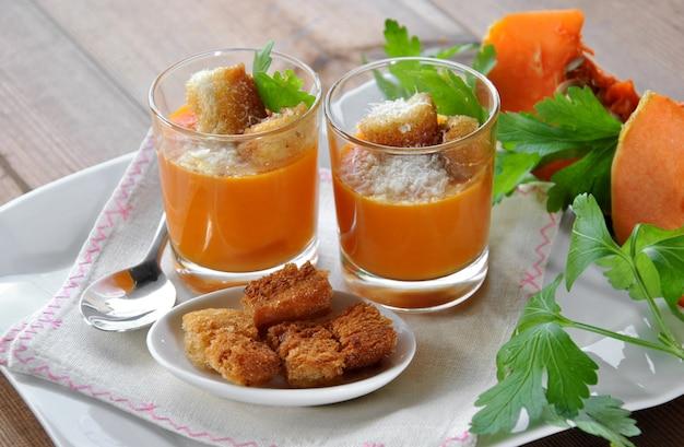 Dois copos com sopa de abóbora e pão e queijo parmesão