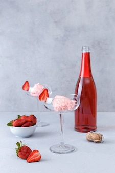 Dois copos com sorvete de morango e champanhe rosa na superfície cinza. conceito de bebidas deliciosas. copie o espaço.