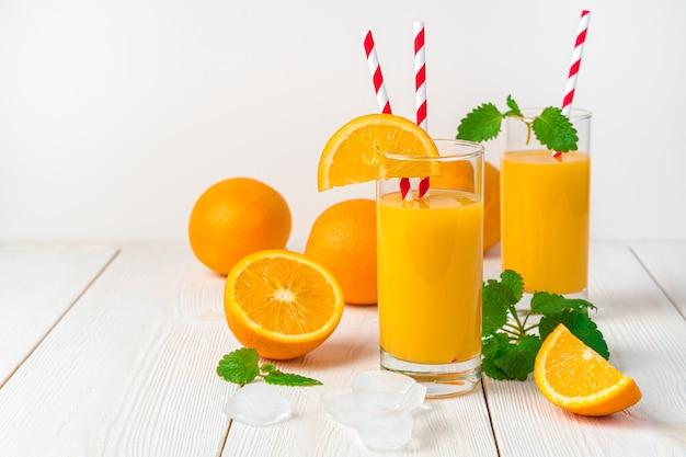 Dois copos com suco de laranja e canudos e laranjas frescas sobre uma mesa leve. vista lateral, horizontal.