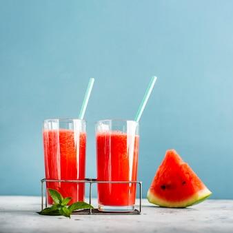 Dois copos com suco de melancia e fatia ao lado