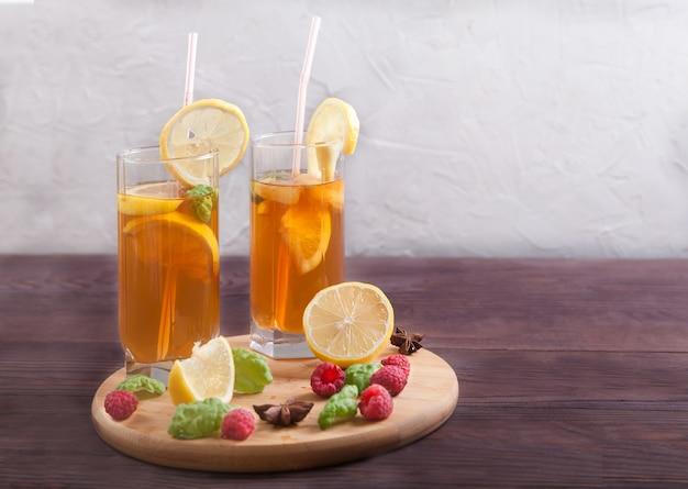 Dois copos com tubo de coquetel com kombuchá e rodelas de limão, canudos e anis estrelado em uma mesa de madeira.