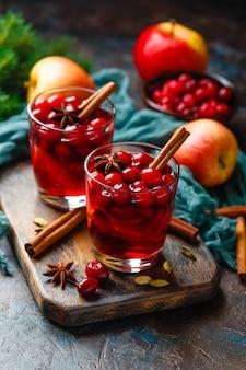Dois copos com uma bebida quente de natal de cranberries e maçãs com especiarias, vinho quente, ponche ou grogue.