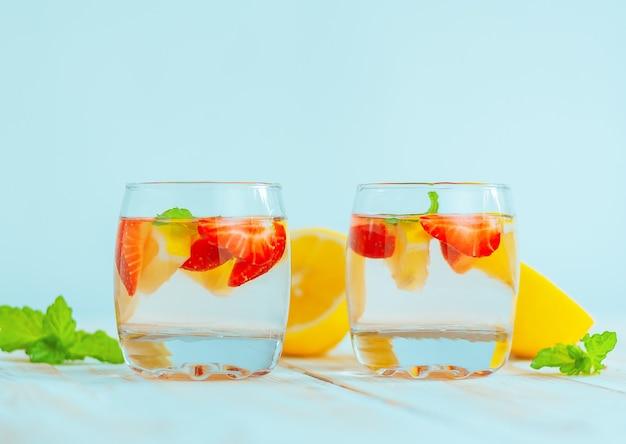 Dois copos com uma bebida refrescante de verão feita de limão, morango e menta. água de limonada. coquetel de frutas cítricas e frutas vermelhas.