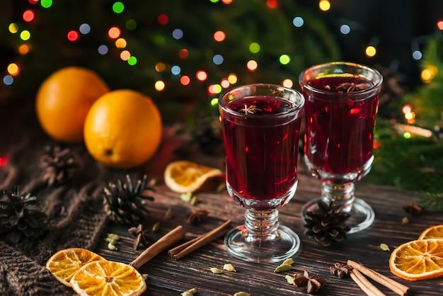 Dois copos com vinho quente na mesa com fatias de laranja e especiarias