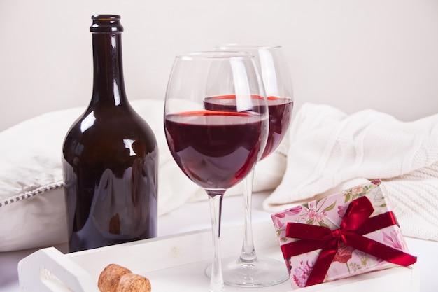 Dois copos com vinho tinto com garrafa e caixa de presente. conceito de jantar romântico.