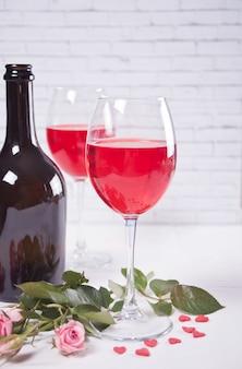 Dois copos com vinho tinto com garrafa e rosas no fundo. conceito de jantar romântico.