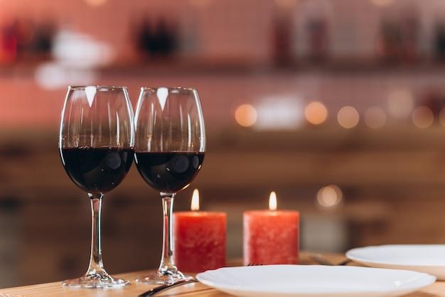 Dois copos com vinho tinto e velas acesas em um close-up de mesa servida