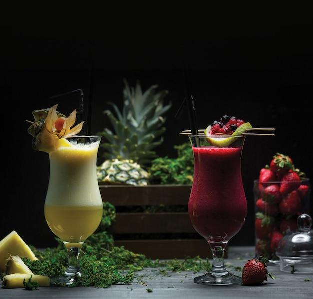 Dois copos de abacaxi e smoothies de morango