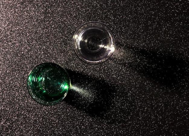 Dois copos de água no fundo preto brilhante