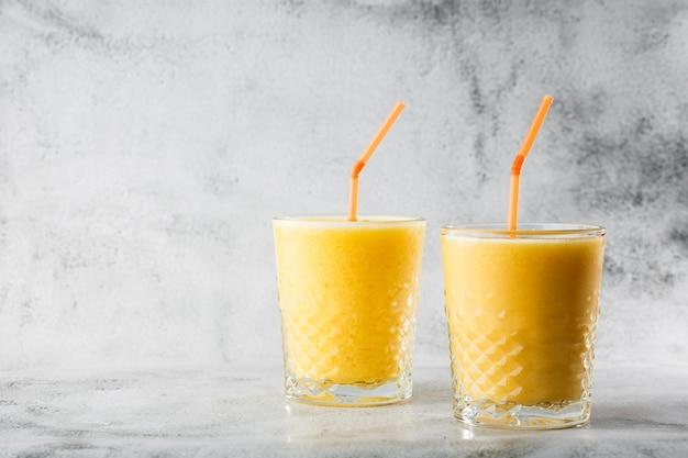 Dois copos de banana amarela, laranja, batidos de manga ou suco de frutas isolados no fundo de mármore brilhante. visão aérea, copie o espaço. publicidade para o menu de café. foto horizontal.