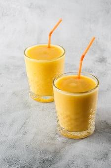 Dois copos de banana amarela, laranja, batidos de manga ou suco de frutas isolados no fundo de mármore brilhante. visão aérea, copie o espaço. publicidade para o menu de café. foto vertical.