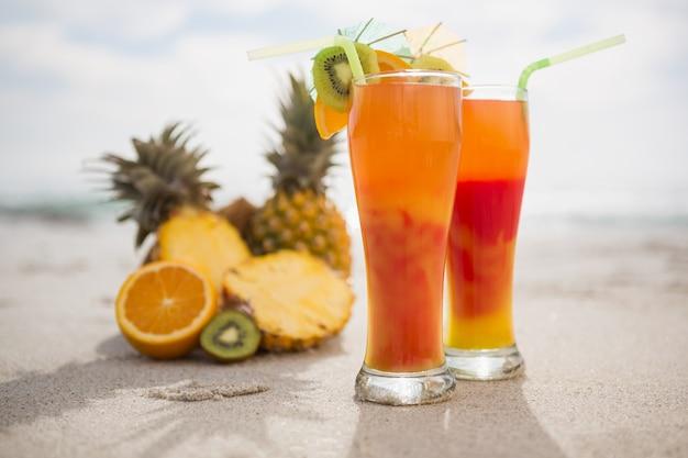 Dois copos de bebida cocktail e frutas tropicais mantidos na areia
