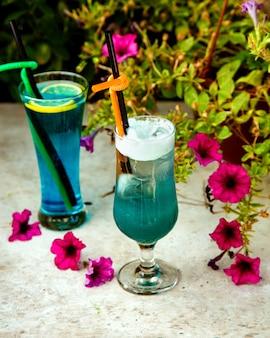 Dois copos de bebidas azuis com canos de palha de plástico