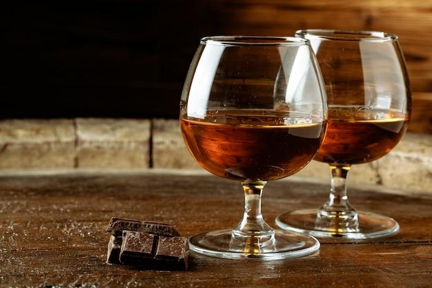 Dois copos de bourbon ou uísque, ou conhaque e pedaços de chocolate amargo