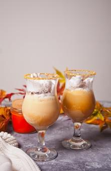 Dois copos de cacau cremoso quente com espuma com folhas de outono e abóboras no fundo