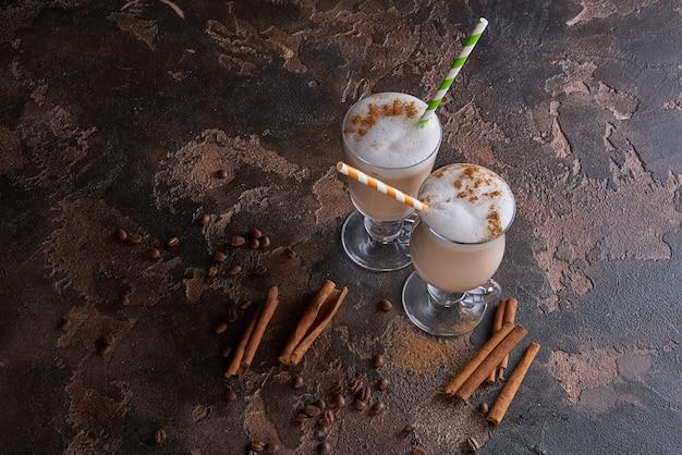 Dois copos de café com leite em uma mesa rústica de madeira com grãos de café e canela
