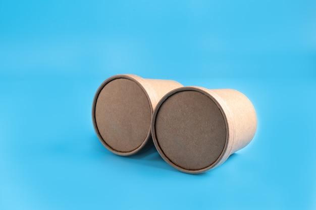 Dois copos de café de papel marrom sobre fundo azul.