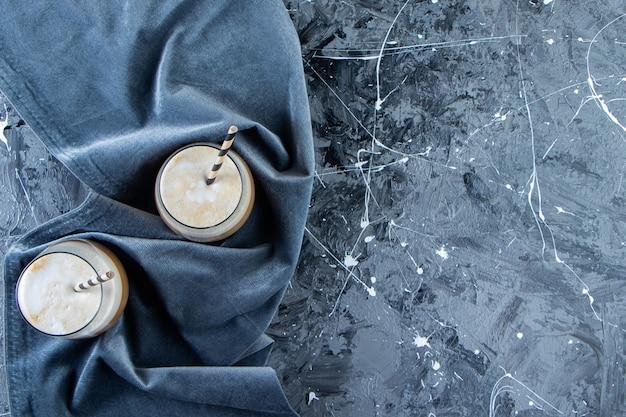 Dois copos de café frio com leite na superfície de mármore.