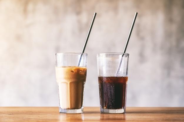 Dois copos de café gelado com canudo de aço inoxidável na mesa de madeira