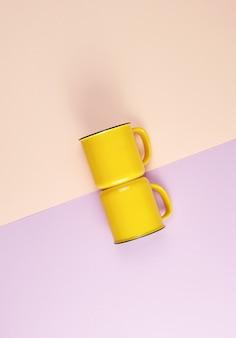 Dois copos de cerâmica amarelos com um identificador em um fundo abstrato pastel