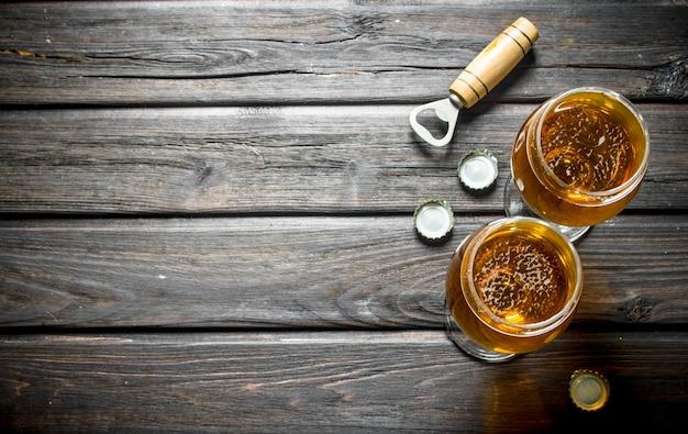 Dois copos de cerveja, abridor e lcovers. em fundo de madeira