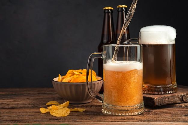 Dois copos de cerveja, batatas fritas e garrafas de cerveja em um fundo marrom. vista lateral, espaço para cópia.