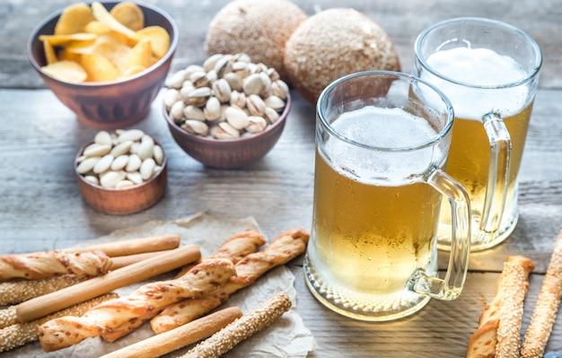 Dois copos de cerveja com aperitivos