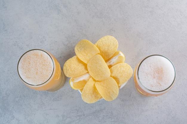 Dois copos de cerveja com batatas fritas em cinza.