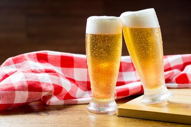 Dois copos de cerveja com espuma brindando ao lado contra uma toalha xadrez na mesa de madeira