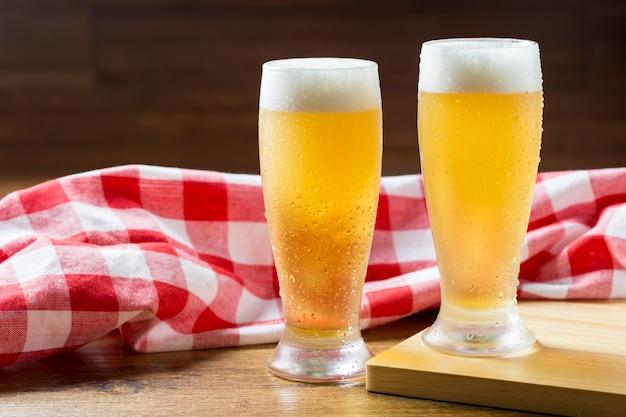 Dois copos de cerveja com espuma contra uma toalha xadrez na mesa de madeira