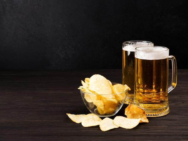 Dois copos de cerveja e batatas fritas e amendoim no escuro de madeira