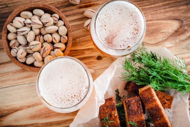 Dois copos de cerveja e pistache em uma mesa de madeira