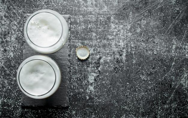 Dois copos de cerveja e tampa. na mesa rústica escura