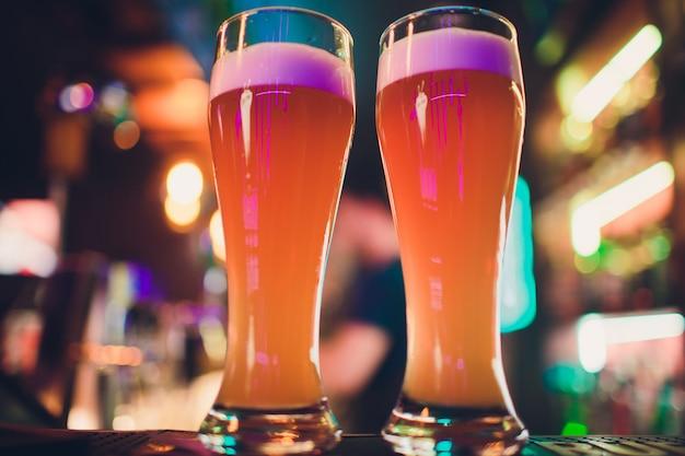 Dois copos de cerveja em uma mesa de bar. torneira de cerveja no fundo.