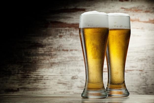 Dois copos de cerveja em uma superfície de madeira vintage