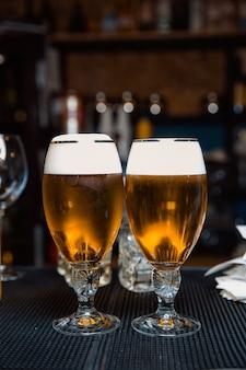 Dois copos de cerveja gelada espumosa em um balcão escuro de bar