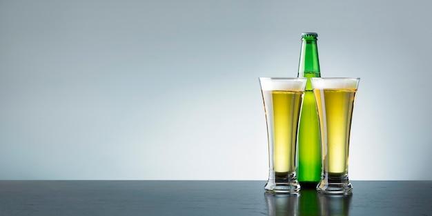 Dois copos de cerveja gelada fresca no balcão escuro com espaço de cópia.