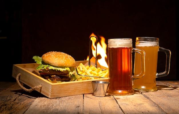Dois copos de cerveja, hambúrguer e batatas fritas na mesa de madeira rústica.