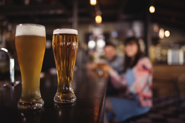 Dois copos de cerveja na bancada