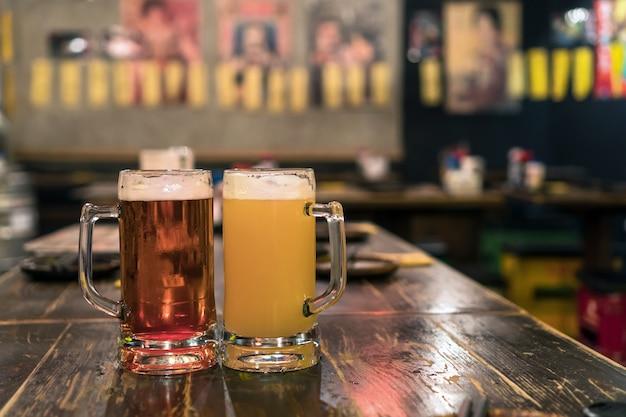 Dois copos de cerveja na mesa de madeira no bar e restaurante. relaxe e beba conceito