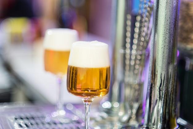 Dois copos de cerveja na torneira de um pub