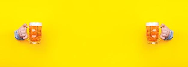 Dois copos de cerveja nas mãos em um amarelo