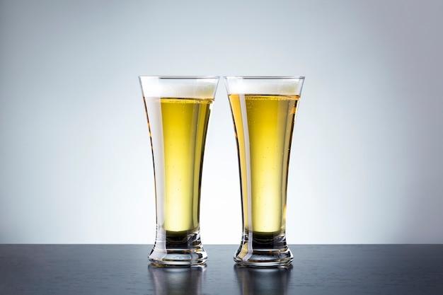 Dois copos de cerveja no balcão escuro contra um fundo cinza com espaço de cópia.